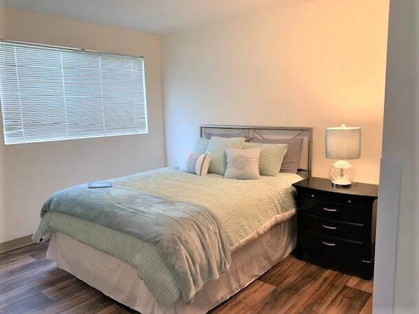 Interior of bedroom with large bed and blinds over window of Parkview 55+ apartment at Daystar Retirement in West Seattle